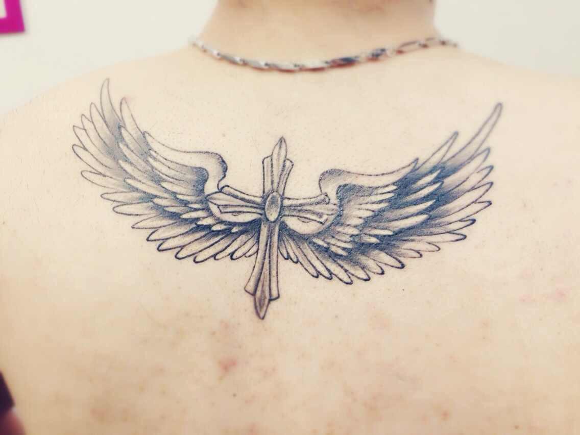 高先生脖子下方纹的带有翅膀的十字架纹身图案